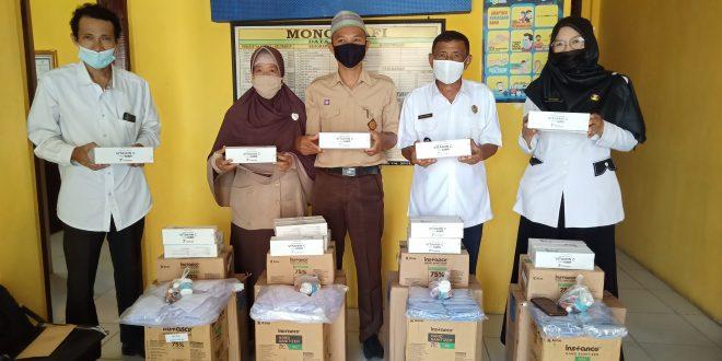 ( Kades Tanjung, Wan Budjang Hairani foto bersama Kepala sekolah pada saat penyerahan alat kesehatan. foto/Ari ))